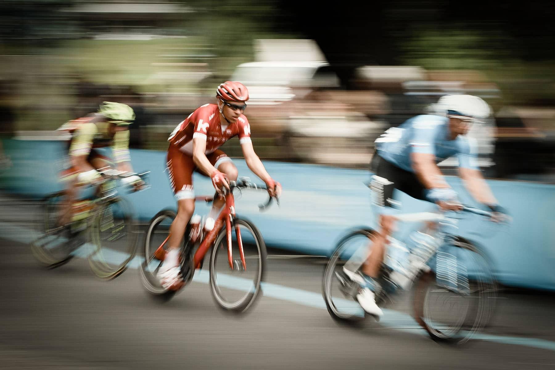 Three men racing on bicycles